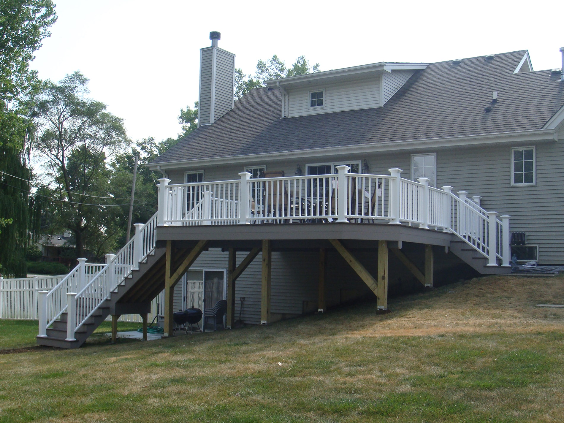 white railing and composite deck installation on sloped yard